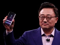 DJ Koh, Samsung's Mobile Communications Business president, holds up new S9Plus devicesduring presentation ceremony in Barcelona