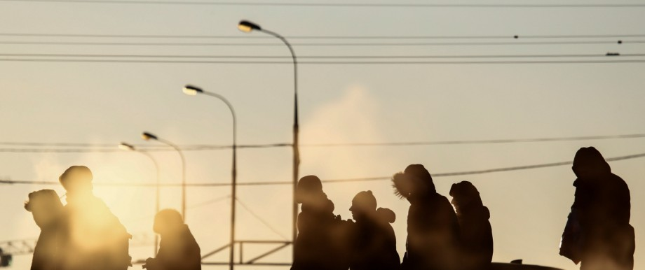 People are silhouetted as they wait at a public transport stop on a frosty winter day in Moscow