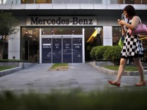 A woman walks past a Mercedez-Benz car dealership in downtown Shanghai