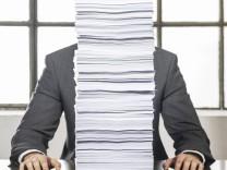 Mann sitzt hinter Papierstapel an Schreibtisch model released Copyright xMEVx ALLMVAID013AR01