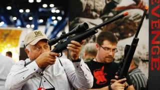 Ein Mann hält auf einer NRA-Veranstaltung ein Gewehr in der Hand