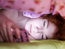 Portrait of girl lying under blanket in bed looking at her smartphone model released Symbolfoto PUBL