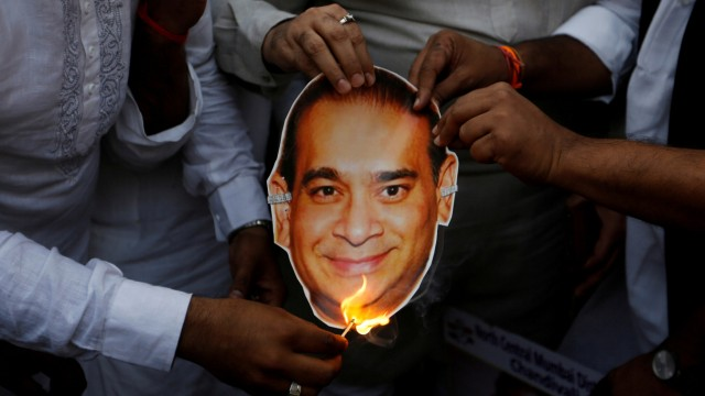 FILE PHOTO: Activists of the youth wing of India's main opposition Congress party burn a cut-out with an image of billionaire jeweller Nirav Modi during a protest in Mumbai