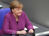 CDU-Bundeskanzlerin Angela Merkel schmunzelt auf der Regierungsbank im Deutschen Bundestag.