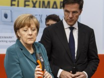 German Chancellor Merkel and Dutch Prime Minister Rutte examine some power cables at stand of German manufacturer 'Lapp' during during opening tour at 'Hannover Messe' industrial trade fair in Hanover