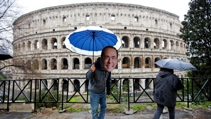An activist wearing a mask of Forza Italia party leader Silvio Berlusconi poses during a tour, the day after Italy's parliamentary election, in Rome