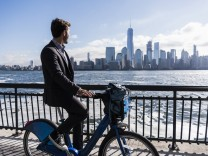 USA man on bicycle at New Jersey waterfront with view to Manhattan model released Symbolfoto PUBLIC