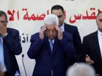 Palestinian President Mahmoud Abbas reads the Koran at the start of Fatah Revolutionary Council meeting in Ramallah, in the occupied West Bank