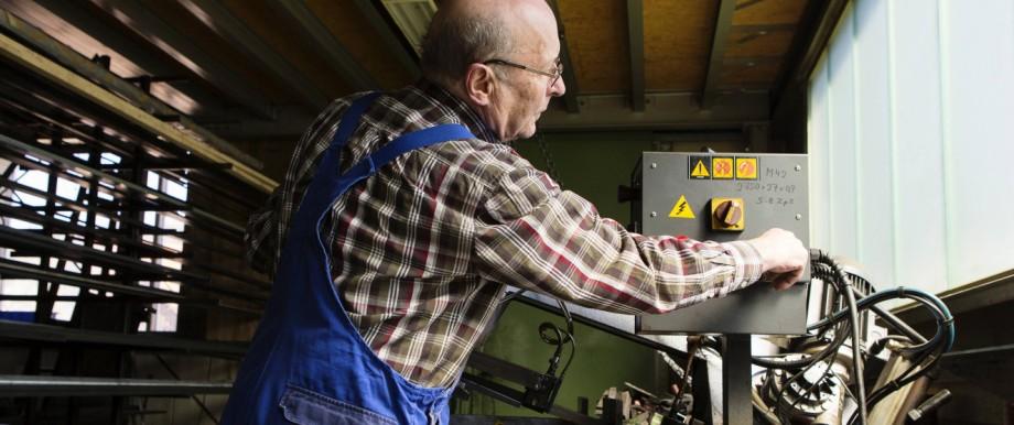 ILLUSTRATION Ein älterer Herr arbeitet in einem mittelständischen Unternehmen für Maschinenbauteile