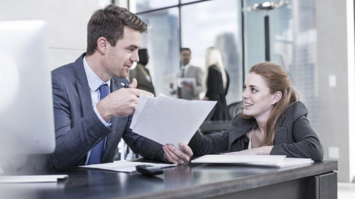 Businessman talking to woman in office model released Symbolfoto property released PUBLICATIONxINxGE