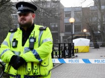 Police officers stand at crime scene tape, as a tent covers a park bench on which former Russian inteligence officer Sergei Skripal, and a woman were found unconscious after they had been exposed to an unknown substance, in Salisbury