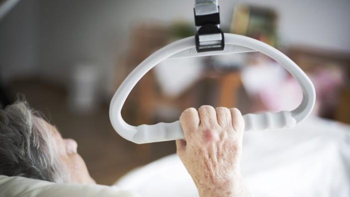 Eine Bewohnerin in einem Altenpflegeheim haelt sich an einem Haltegriff fest 04 08 2017 Eberswalde