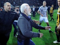 Russian-born Greek businessman and owner of PAOK Salonika, Ivan Savvides , pictured with what appears to be a gun in a holster, enters the pitch after the referee annulled a goal of PAOK during their soccer match against AEK Athens in Toumba Stadium in Th