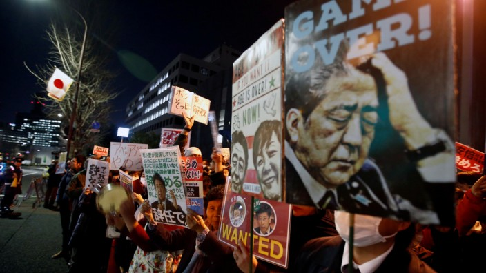 Protesters shout slogans with placards denouncing Japanese Prime Minister Shinzo Abe at a rally in Tokyo