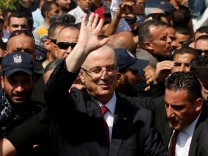 FILE PHOTO: Palestinian Prime Minister Rami Hamdallah waves upon his arrival, in the northern Gaza Strip