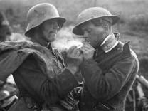 Ein deutscher Gefangener gibt einem britischen Verwundeten (re.) Feuer. Die Aufnahme entstand an der Westfront im Jahre 1918.