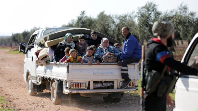Internally displaced people ride on the back of a truck in the town of Inab