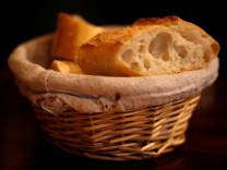 Pieces of French baguette are seen in a bread basket displayed on a table of a restaurant in Paris