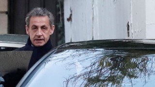 Former French President Nicolas Sarkozy enters his car as he leaves his house in Paris