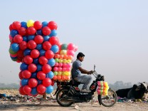 A man carries children's coloured plastic balls on his motorcycle in Delhi