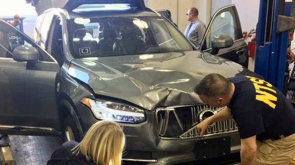 FILE PHOTO: NTSB investigators examine a self-driving Uber vehicle involved in a fatal accident in Tempe