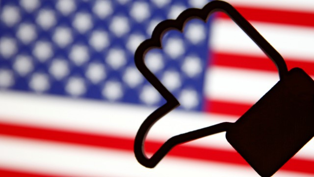 A 3D-printed Facebook Like symbol is displayed inverted in front of a U.S. flag in this illustration