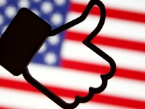 A 3D-printed Facebook Like symbol is displayed in front of a U.S. flag in this illustration