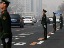 Security personnel take position along Beijing's main east-west thoroughfare, Changan Avenue, in Beijing