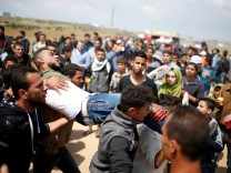 Wounded Palestinian is evacuated during clashes with Israeli troops, during a tent city protest along the Israel border with Gaza, demanding the right to return to their homeland, east of Gaza City
