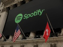 The Spotify logo hangs on the facade of the New York Stock Exchange with U.S. and a Swiss flag as the company lists it's stock with a direct listing in New York