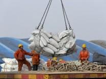 China: Arbeiter verladen Säcke mit Sojabohnen
