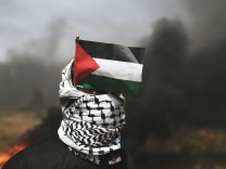 Demonstrator with a Palestinian flag looks on during clashes with Israeli troops at the Israel-Gaza border at a protest demanding the right to return to their homeland, in the southern Gaza Strip