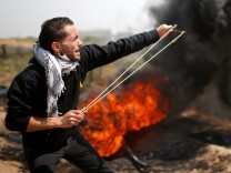 Palestinian demonstrator hurls stones at Israeli troops during clashes at the Israel-Gaza border east of Gaza City
