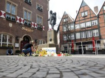 A woman places a candle at the site where on April 7, a man drove a van into a group of people sitting outside a popular restaurant in the old city centre of Muenster