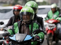 FILE PHOTO: Driver and passenger ride on a motorbike, part of the Go-Jek ride-hailing service, on a busy street in central Jakarta