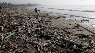 A local resident walks along a section of Matahari Terbit beach covered in plastic and other debris washed ashore by seasonal winds near Sanur, Bali