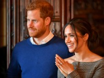 FILE PHOTO: Britain's Prince Harry and his fiancee Meghan Markle watch a performance by a Welsh choir in the banqueting hall during a visit to Cardiff Castle in Cardiff