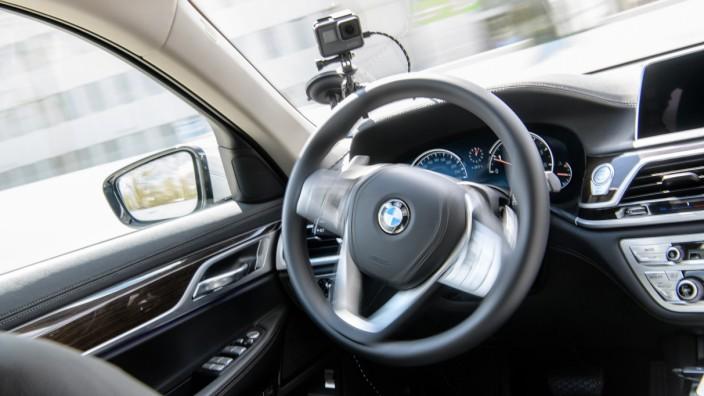 Das Lenkrad eines selbstfahrenden BMW dreht sich, ohne dass ein Mensch am Steuer sitzt.