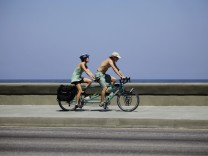 Tourists ride a tandem bicycle along Havana's seafront boulevard 'El Malecon'