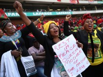 Women cheer during eulogies at Winnie Madikizela-Mandela's funeral in Orlando stadium in Soweto
