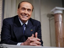 Forza Italia leader Berlusconi smiles as League party leader Salvini (not seen) speaks following a talk with Italian President Sergio Mattarella at the Quirinale palace in Rome