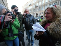 ST PETERSBURG RUSSIA APRIL 13 2018 A flashmob participant poses with a paper plane bearing the