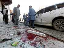 Afghan men inspect the site of a suicide bomb blast in Kabul