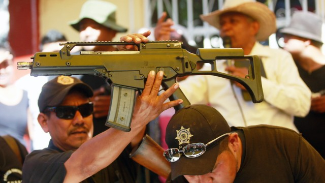 An assault rifle, which was seized from a house during an operation, is held up by a member of the Community Police of the FUSDEG during a presentation in the village of Petaquillas