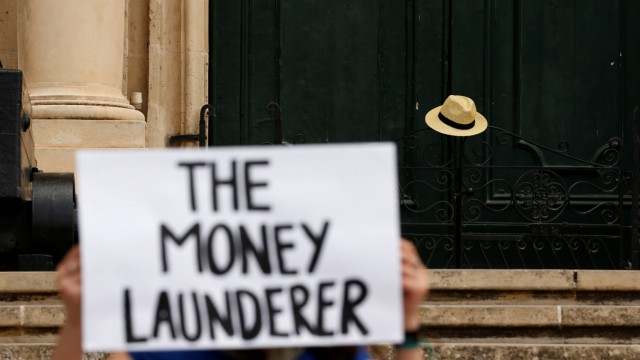 Activists from anti-corruption group Il-Kenniesa (The Sweeper) protest outside the office of Prime Minister Joseph Muscat at Auberge de Castille in Valletta
