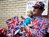 A supporter of the royal family holds a doll wearing a crown as he sits outside the Lindo Wing of St Mary's Hospital after Britain's Catherine, the Duchess of Cambridge, was admitted after going into labour ahead of the birth of her third child, in London