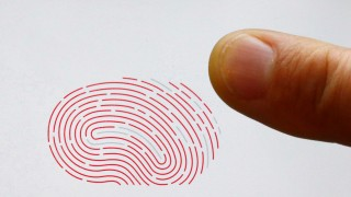 A person uses a sensor for biometric identification on a smartphone in Berlin