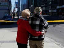 A couple look down the road after an incident where a van struck multiple people at a major intersection in north Toronto