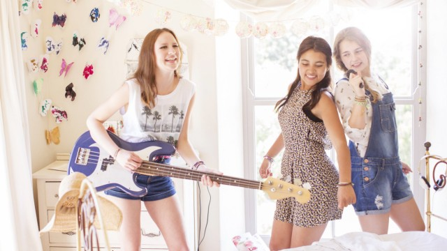 Girls playing music and singing Three teenage girls playing music and singing in bedroom PUBLICATIO