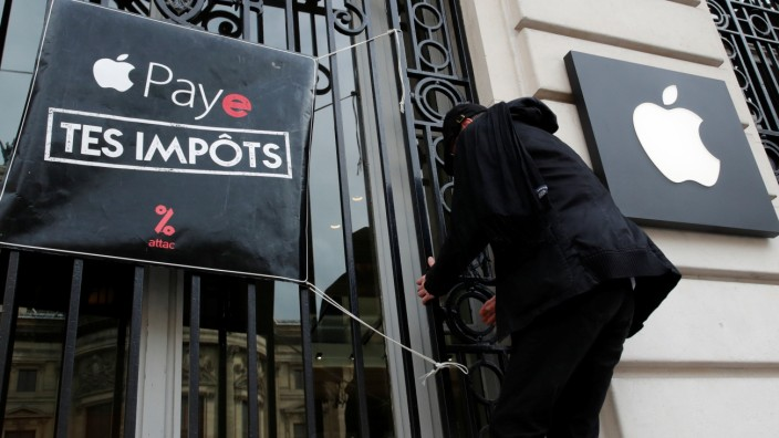 Attac activist hangs poster in front of Apple store in Paris